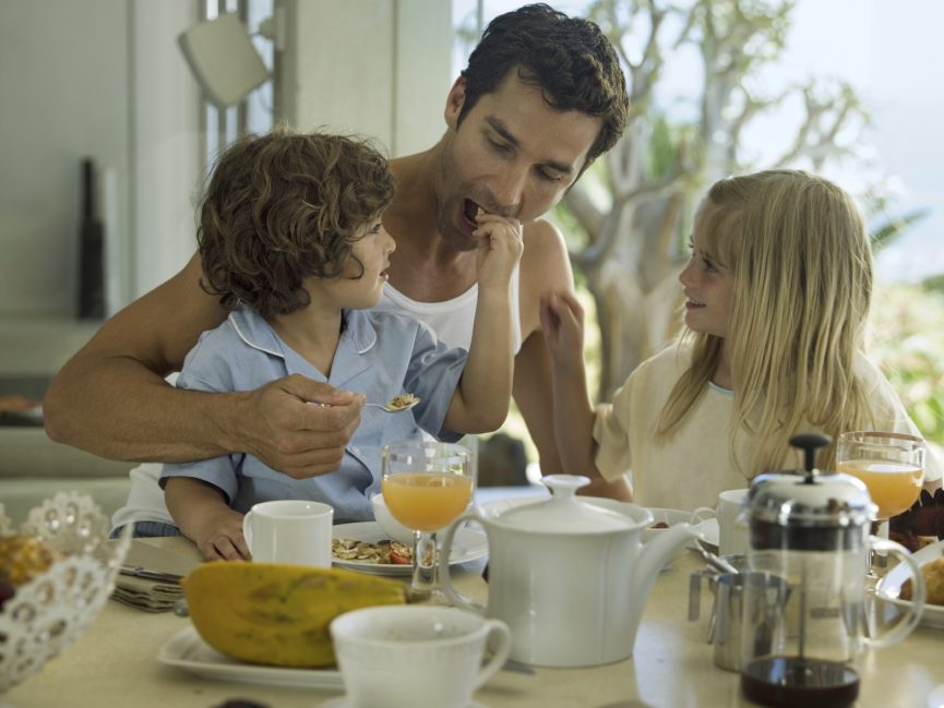 Children feeding their father breakfast.