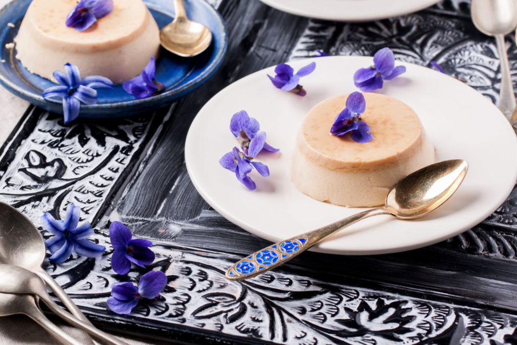 27319961 - plate with caramel pannacotta served with violet flowers over black and white table
