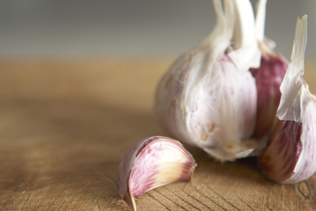 Macro image of fresh garlic on rough wooden chopping board Shallow focus.