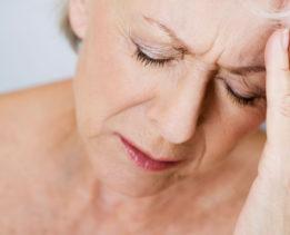 B7MHB7 A senior woman with a headache, touching her forehead