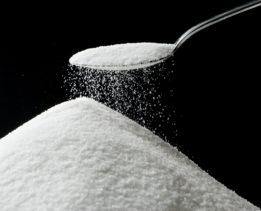 Sugar falling from Silver Spoon. Focus on edge of spoon sugar pile top.