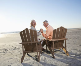 Senior couple (60s) sitting on beach, holding hands.