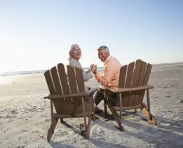Senior couple (60s) sitting on beach, holding hands.