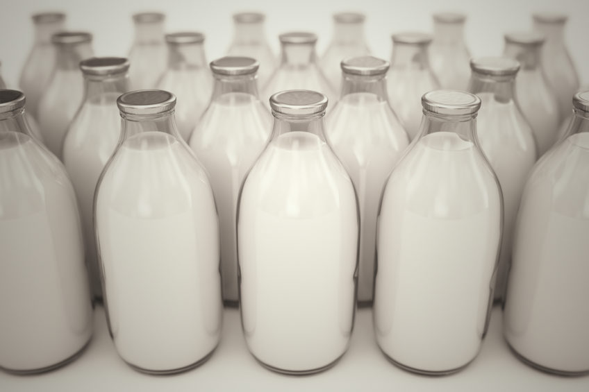 Front shot of old-fashioned glass bottles filled with milk on a white backround. Perfect for any health or natural nutricion realted purposes.