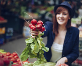 Young Female Buying Radishes At Market Place. Focus Is On Radishes