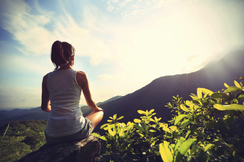 young yoga woman at sunrise mountain peak