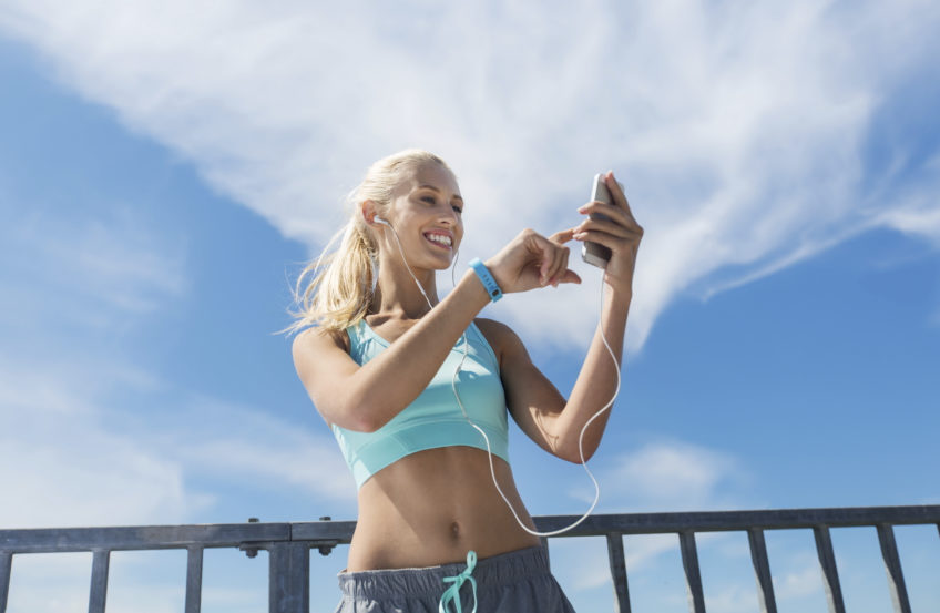fitness, sport, people, technology and healthy lifestyle concept - smiling young woman with smartphone and earphones listening to music and exercising outdoors