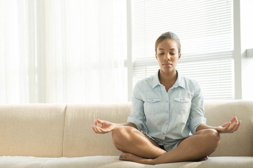 Copy-spaced image of a black woman meditating at home