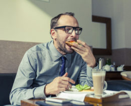 Businessman eating breakfast at home/hotel. Indoor photo