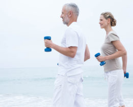 Fit couple lifting dumbbells at the beach