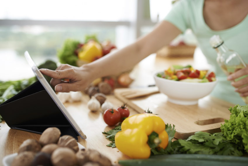 Woman checking recipe on digital tablet before seasoning salad