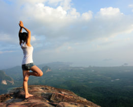 young woman  mountain peak cliff  practice yoga