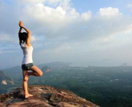 young woman  mountain peak cliff  practice yoga
