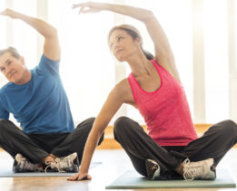 Fit mature couple practicing yoga on mat. Man and woman are doing stretching exercise. They are in sports clothing, in brightly lit apartment.
