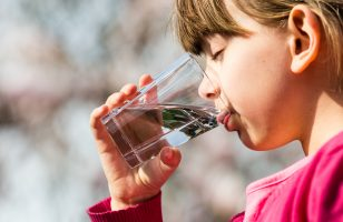 Young girl holding glass and drinking pure water. Ideal for environmental protection or future generations concept.