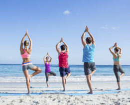 Friends doing yoga together with their teacher at the beach