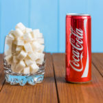 KIEV, UKRAINE - MAY 8, 2015: Can of Coca-cola and a glass of sugar.