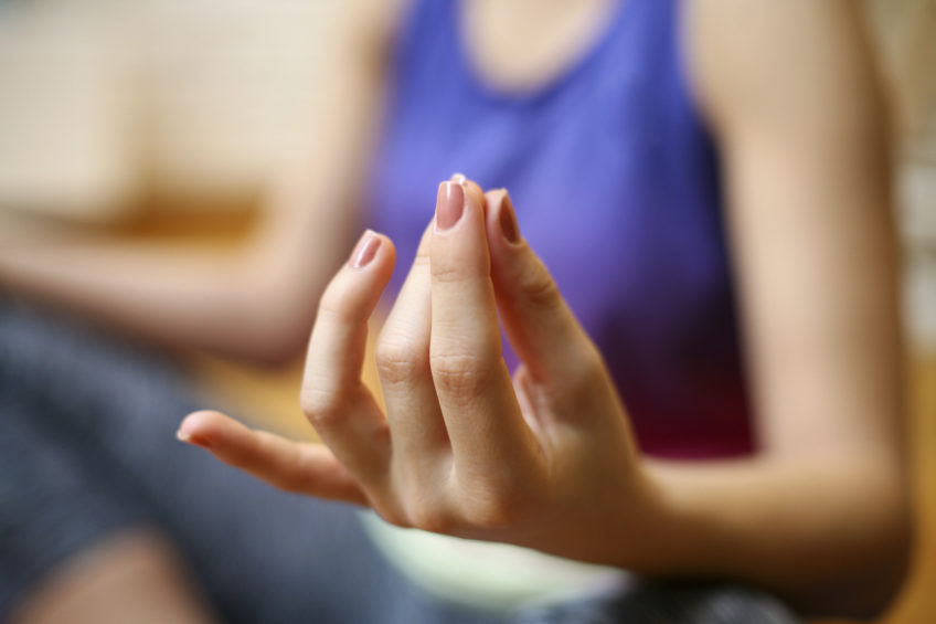 Woman meditating at home, practicing yoga.