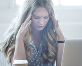 Stressed business woman working on a laptop. She is casually dressed in an office with a large window. She looks very uncomfortable and could also have a headache. She is holding her hands to her temples and looking very upset. Copy space.