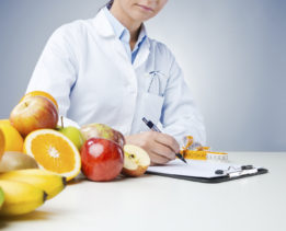 Professional nutritionist working at desk and writing medical records with fresh fruit on foreground