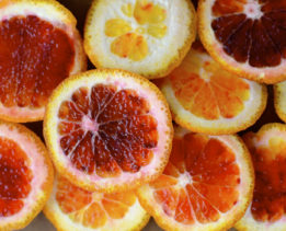 Blood oranges that have been cut in half, basking in the glow of natural light.